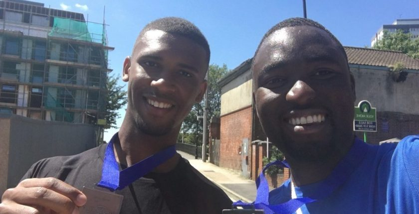 Nathan Longe and Uche Monago smiling after completing a 10k charity run with their medals