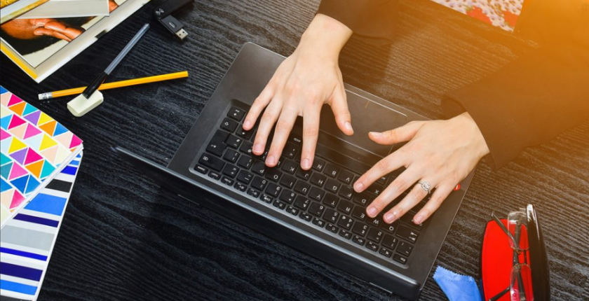 Person typing at a laptop at a desk