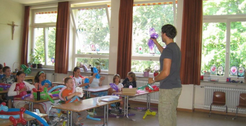 Male teacher standing in front of a class of young pupils